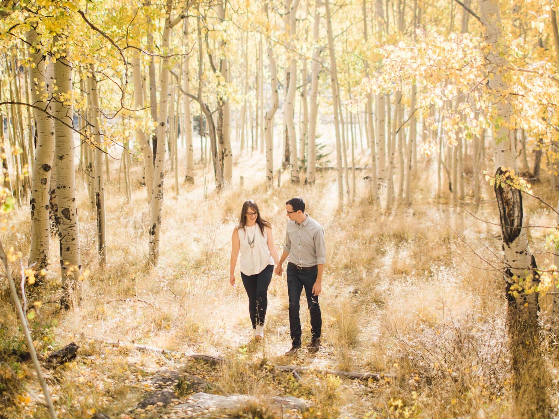 couple walking through golden aspens in colorado