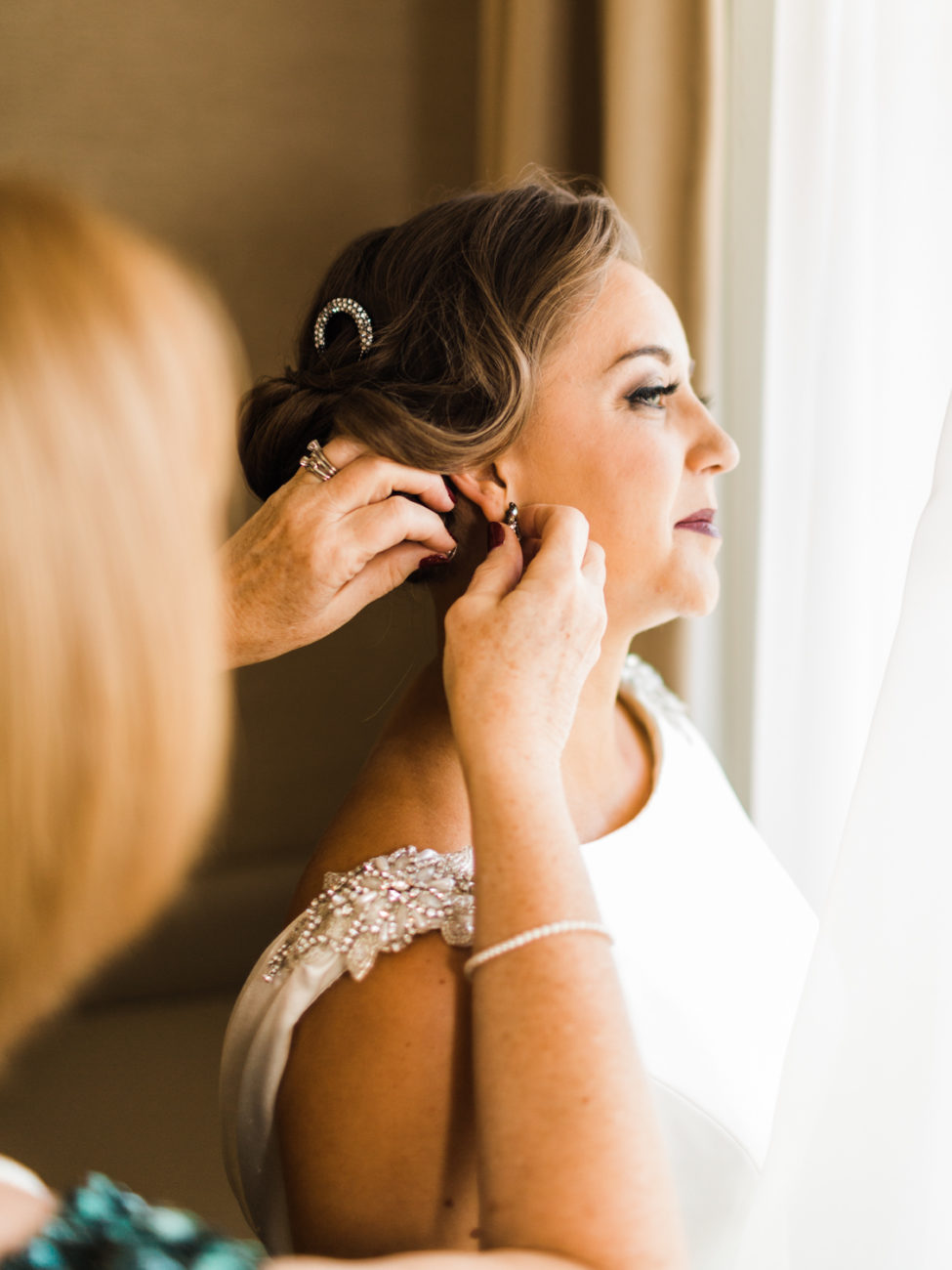 bride and mother putting earrings on
