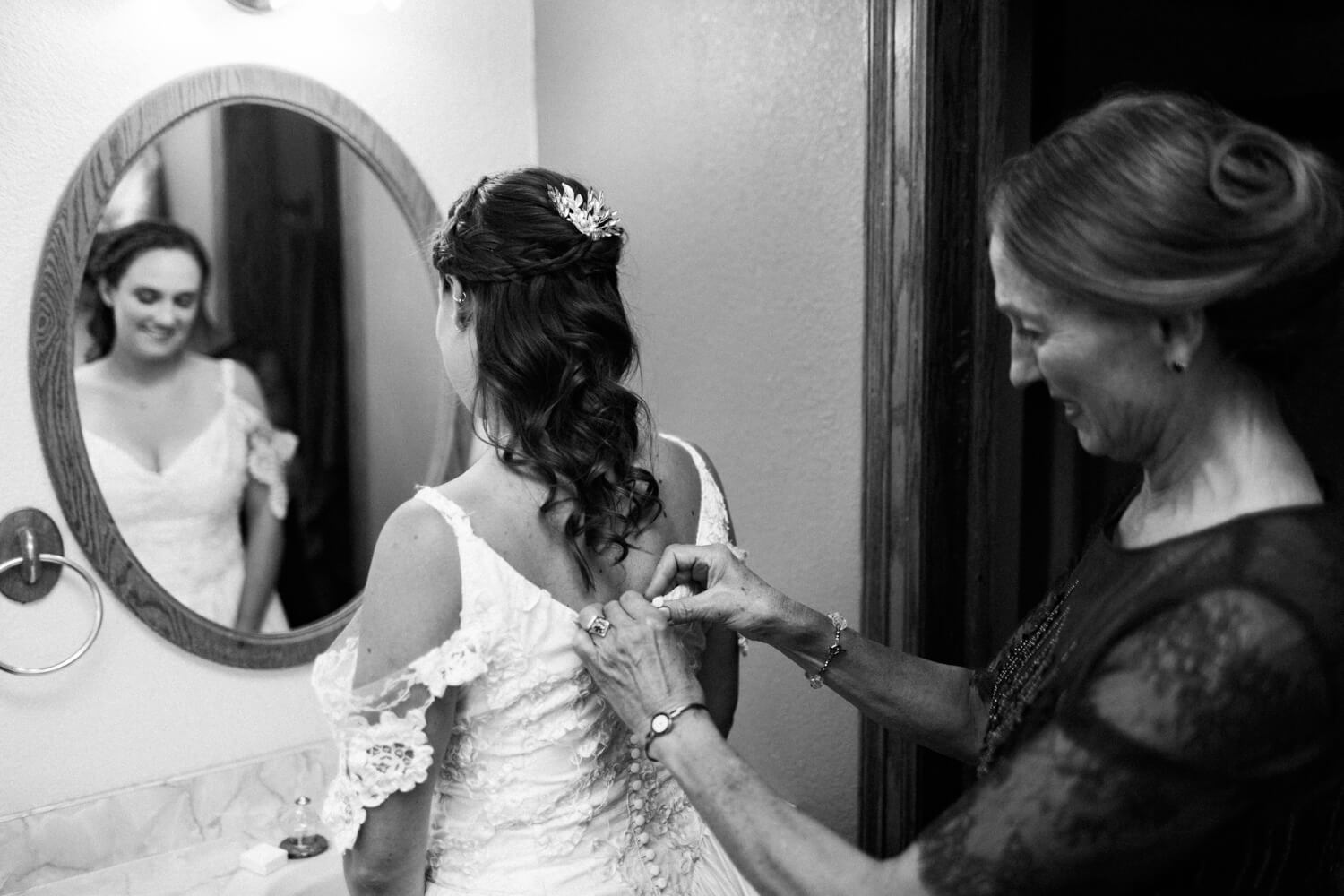mother of the bride buttoning dress as bride looks into mirror