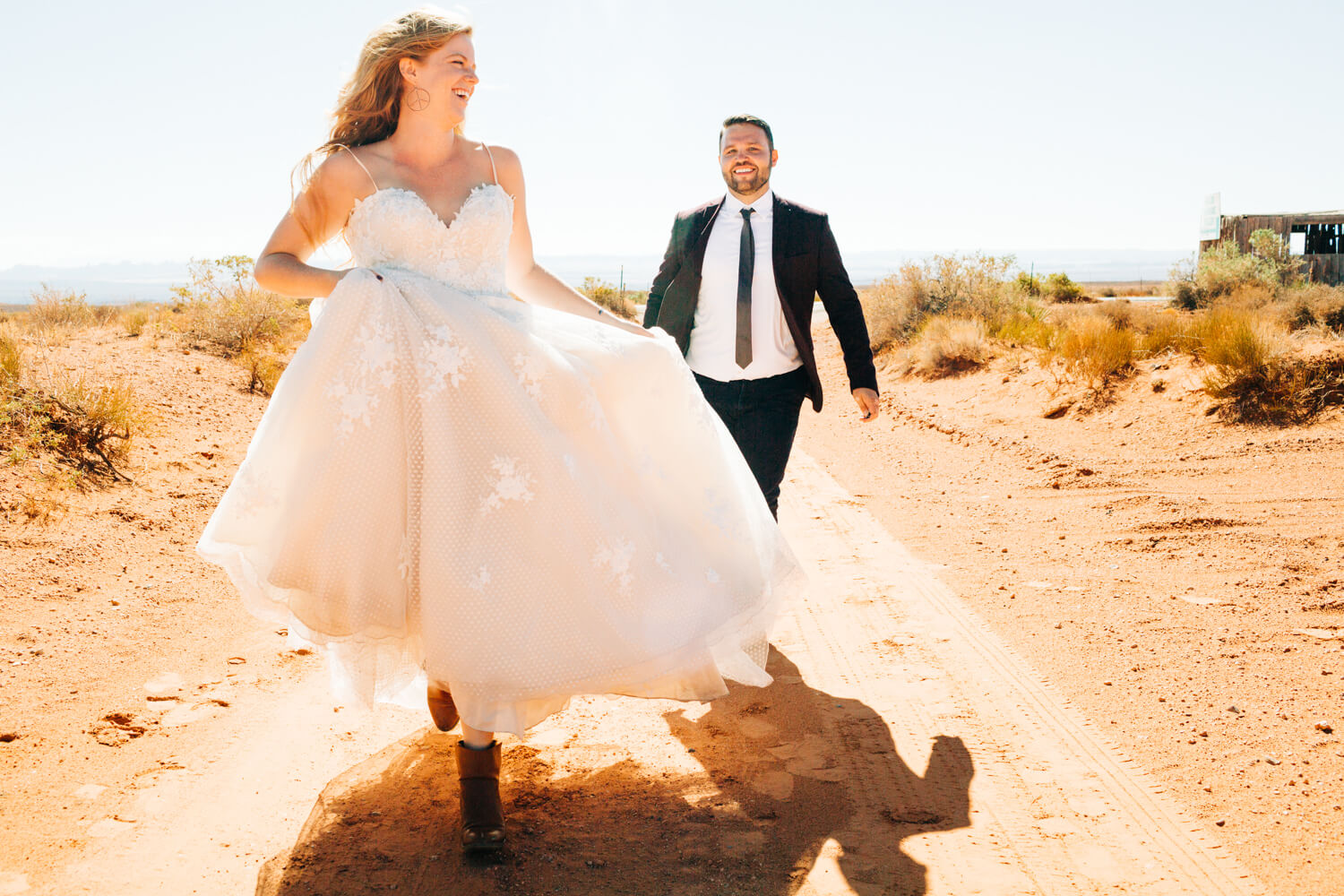 bride and groom running through the desert