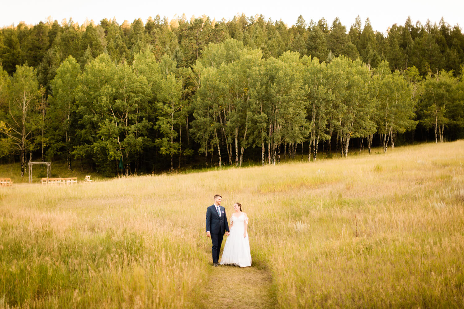 bride and groom just married walking through a meadow