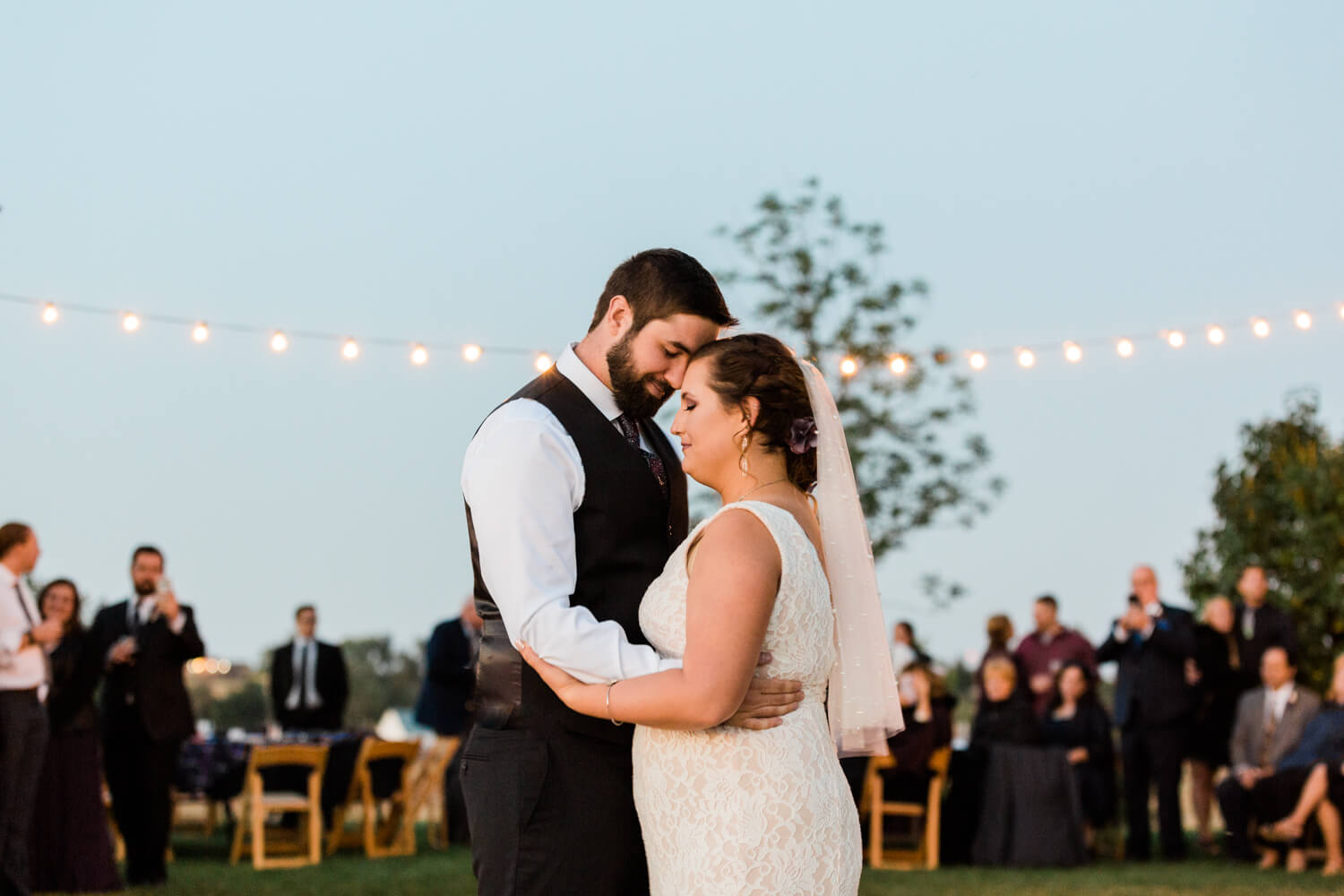 bride and groom first dance under twinkle lights