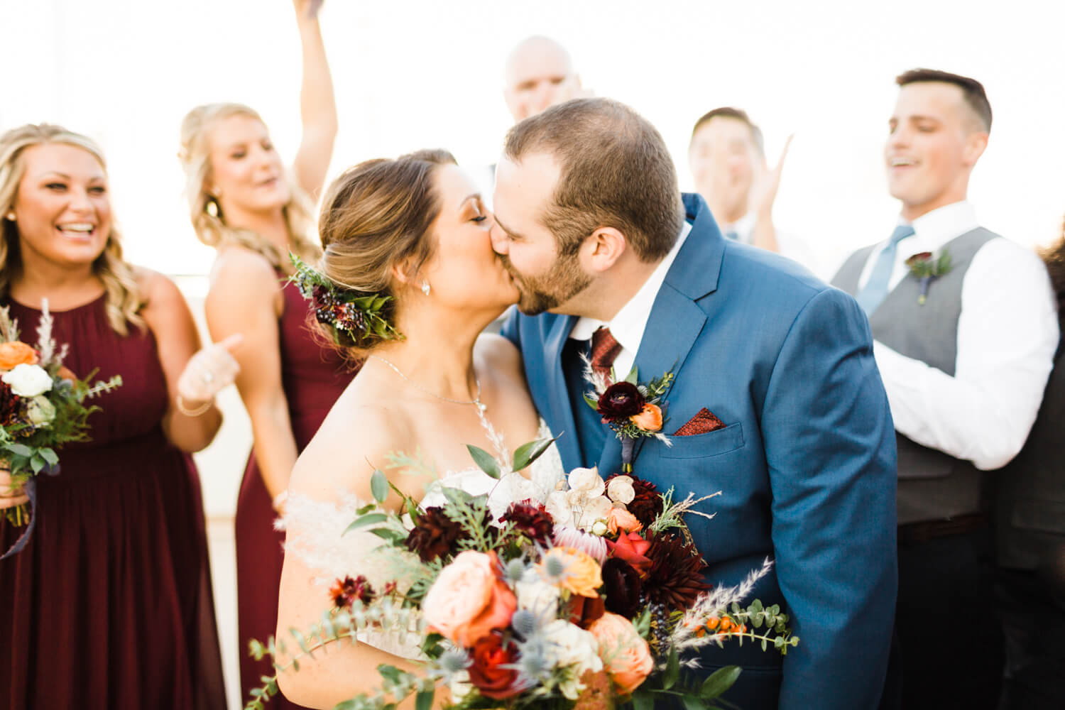 bride and groom kissing with friends cheering behind