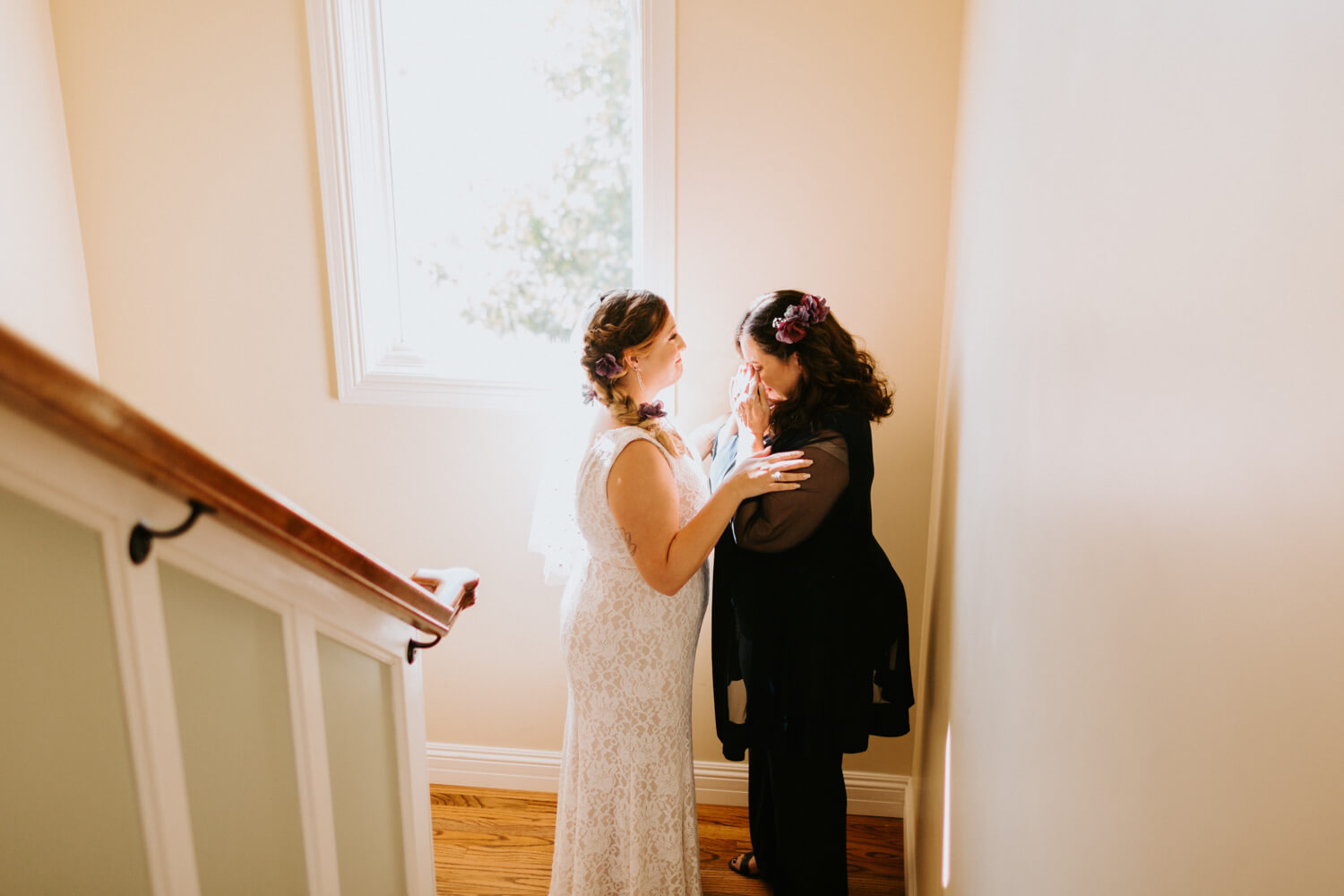 mother of the bride crying with bride in a stairwell