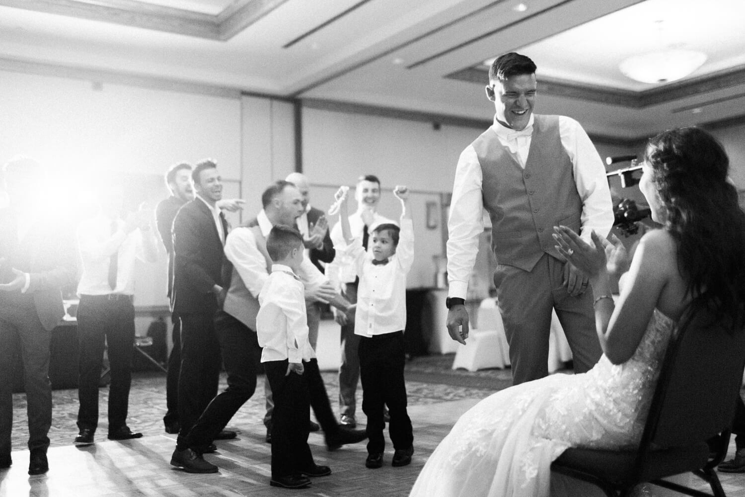 a kid catching the garter during the garter toss as the groom laughs with bride