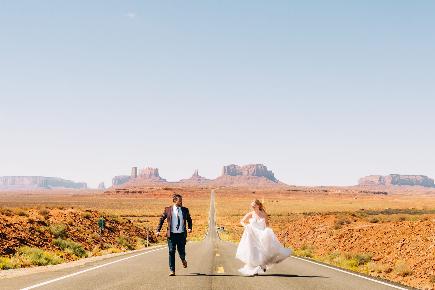 bride and groom running in front of monument valley