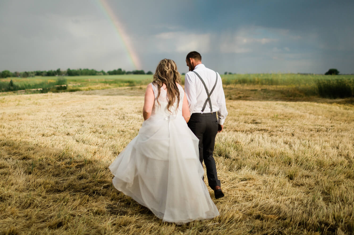 bride and groom walks away from the camera toward a rainbow