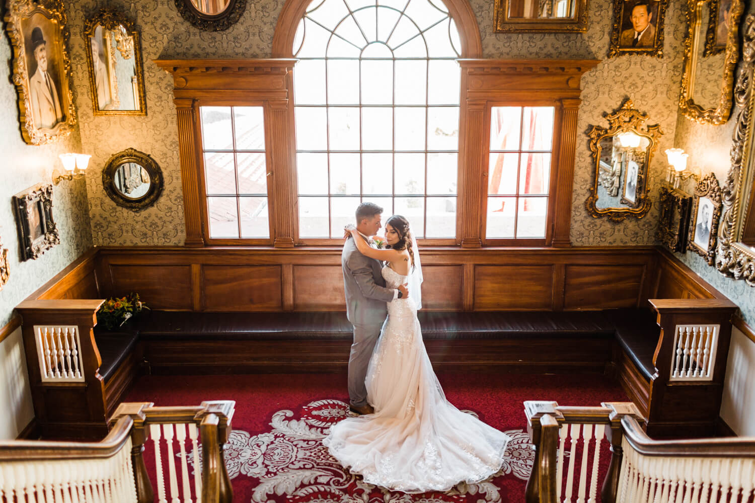 bride and groom in front of an ornate wall