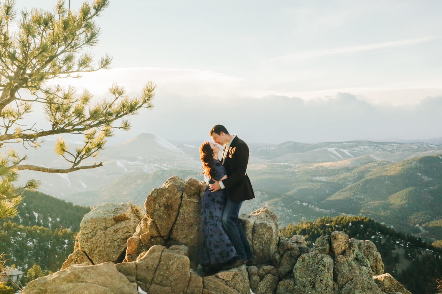 couple kissing in front of a mountain range in colorado