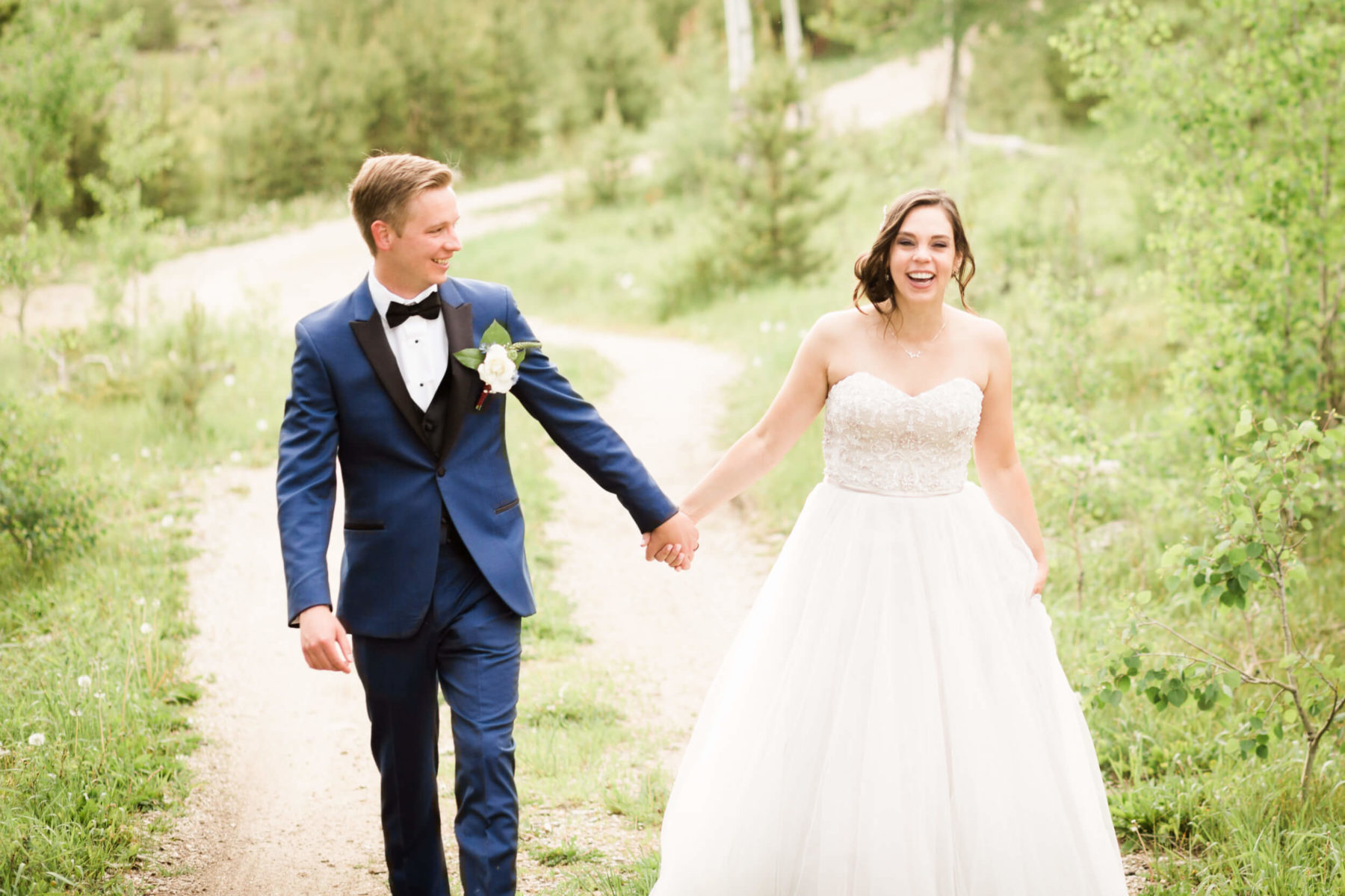 bride and groom laughing in colorado mountains
