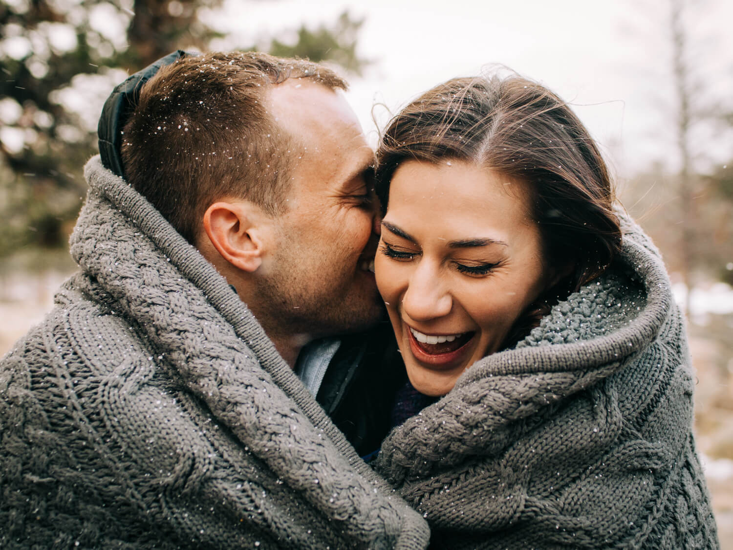 man and woman laughing in the snow together