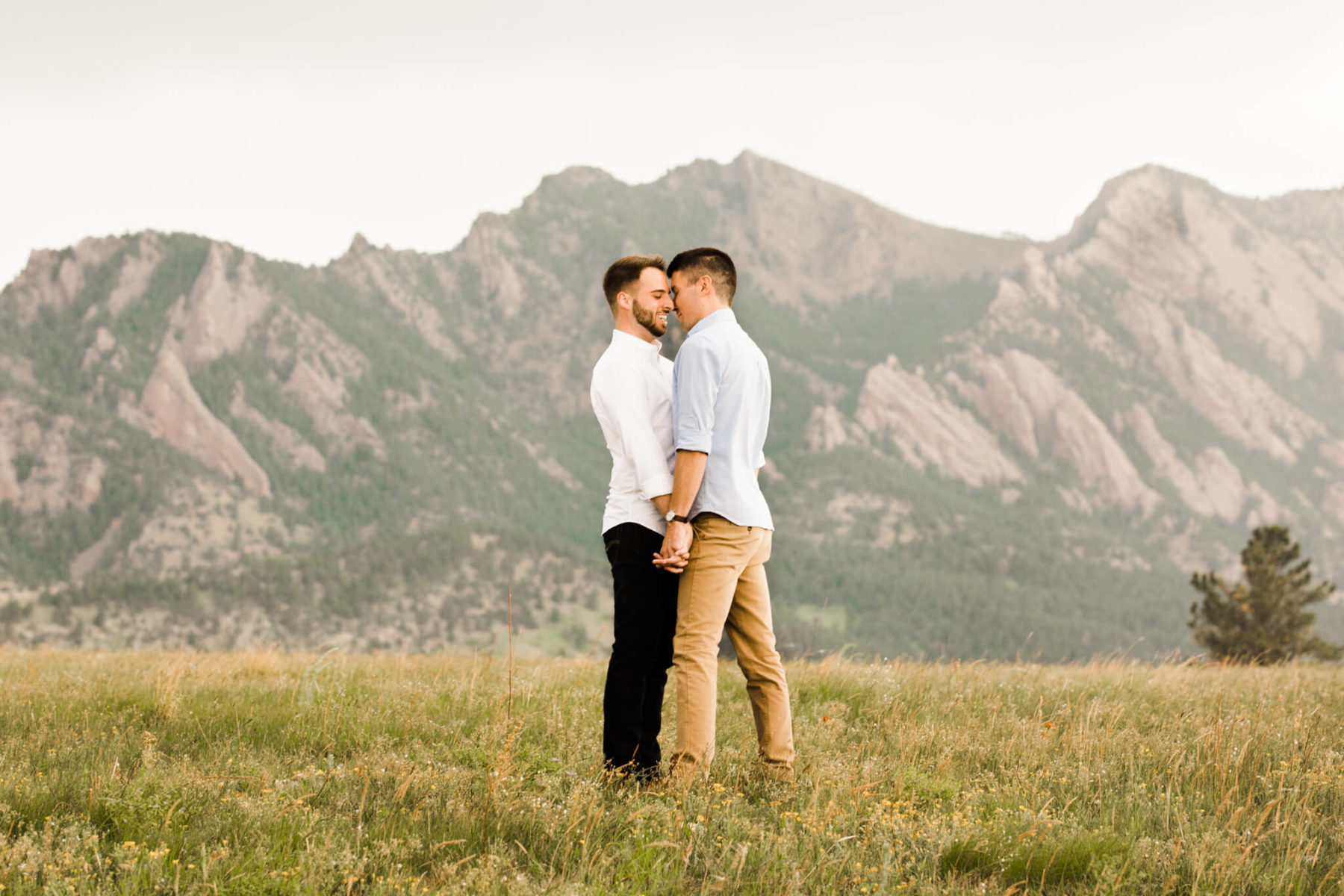 gay couple kissing in front of a mountain range in colorado | engagement photography