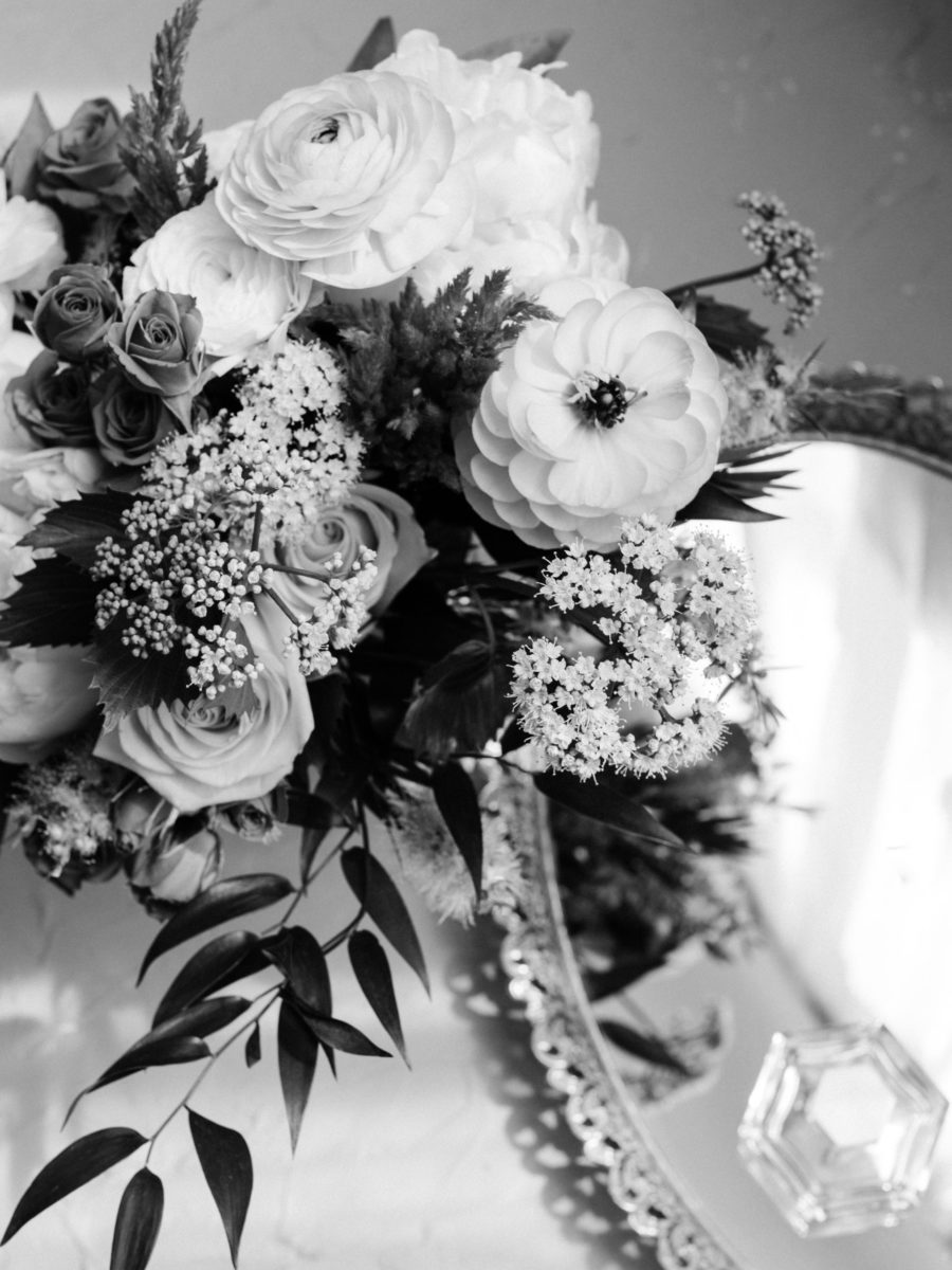 flowers positioned above a flat antique mirror