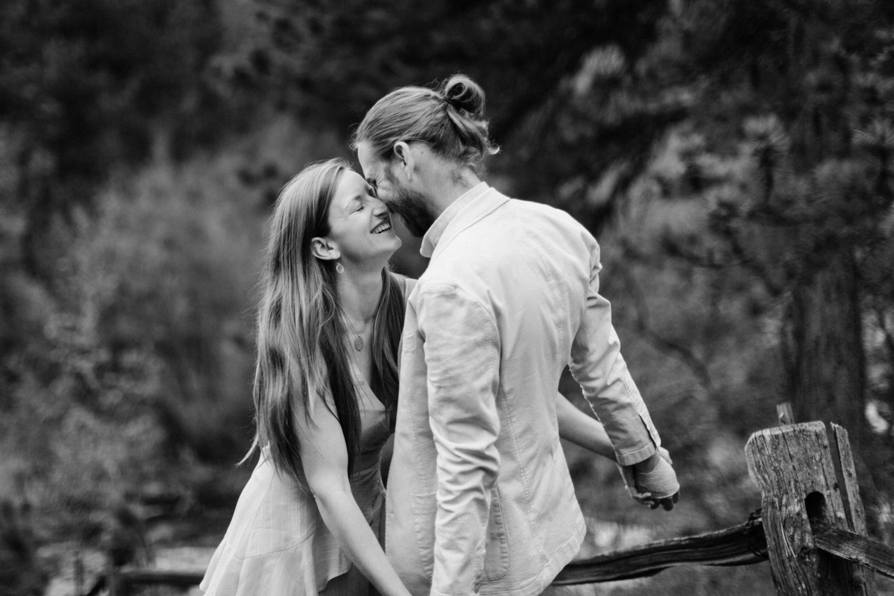 couple kisses in the mountains during an engagement session