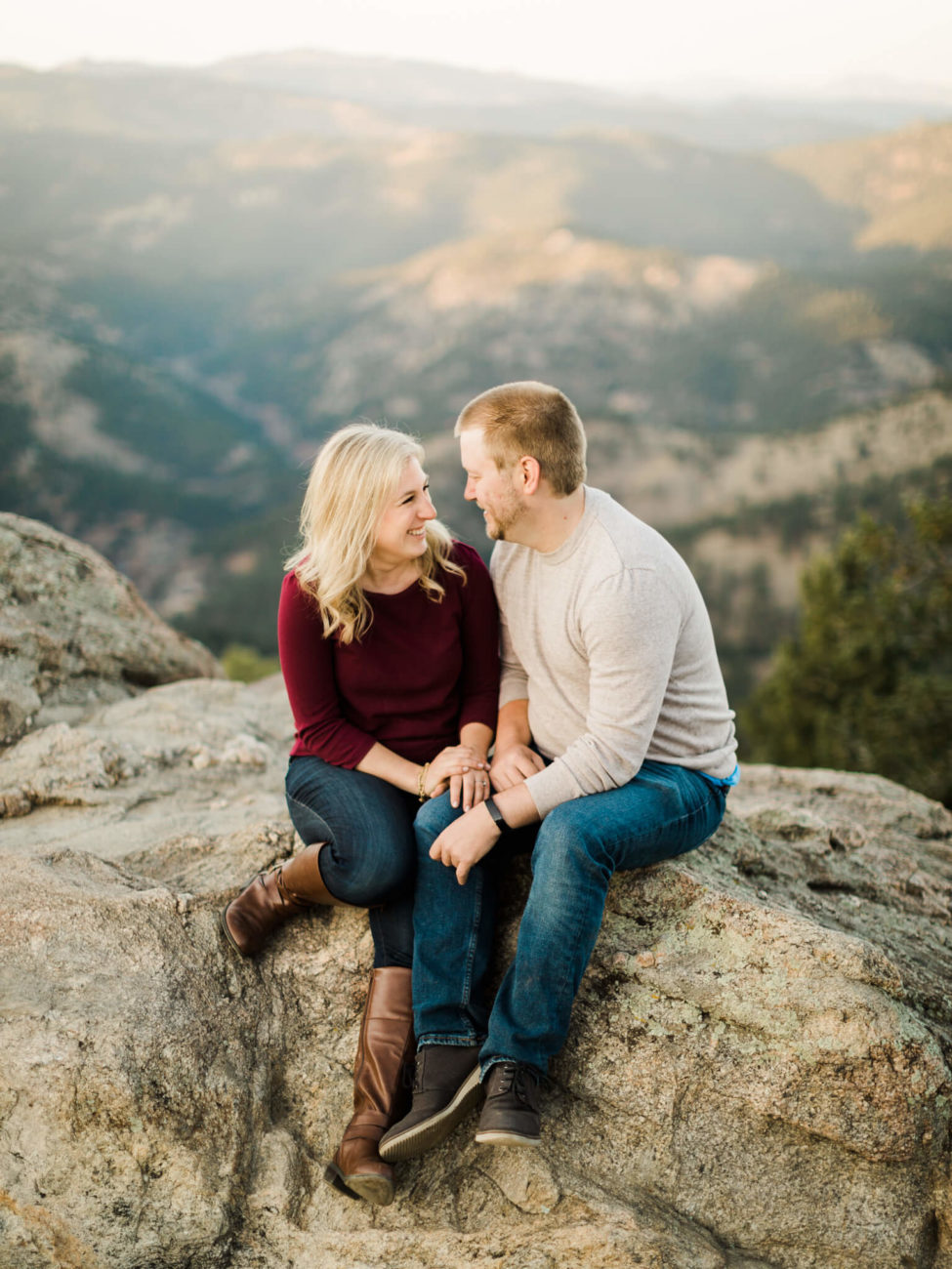 couple sitting on a rock on the top of a mountain in boulder colorado
